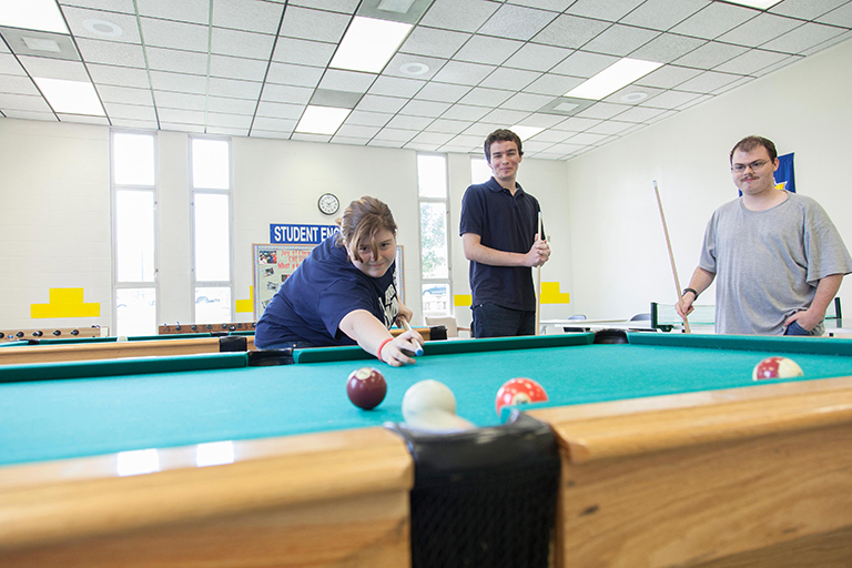 Three students playing pool