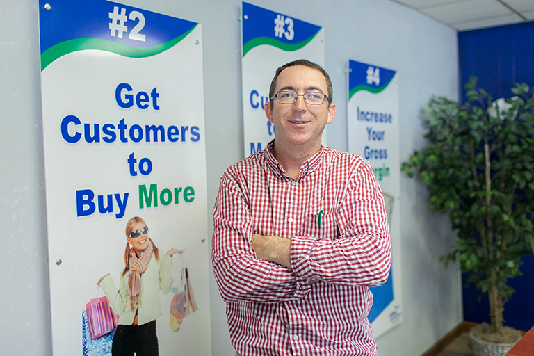 Man posing in front of marketing/business banners